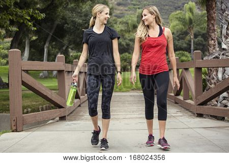 Two attractive women in their 30s talking a walk or jog together in the outdoors. Cute blond and fit women who are active and working to stay healthy.