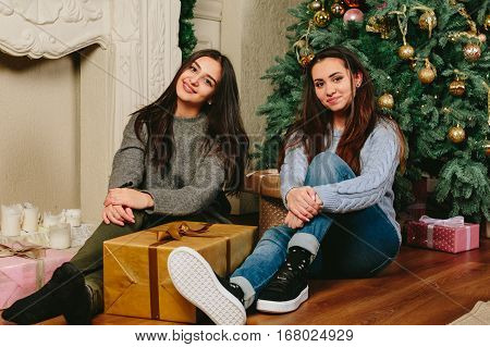 Two beautiful young girls sitting on the floor near a Christmas tree. studio horizontal photo.