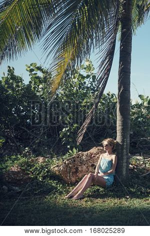 Lovely girl in a blue dress, posing sitting in the shade of palm trees. The general plan of the girl sitting on the stone tease trees and flowing hair on the wind. The sun penetrating through the leaves of palm leaves shadow on the face of the model.