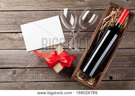Valentines day greeting card. Wine and gift box on wooden table. Top view with copy space