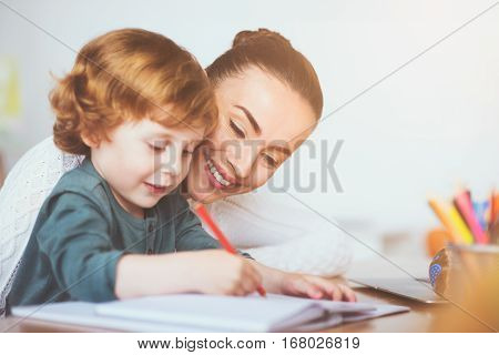 Well done. Delighted happy young mother teaching her small son to write while sitting on the table and smiling.