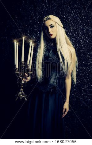 Beautiful gothic lady in long black dress standing with candles in the dark. Middle Ages. Vampires. Halloween concept.