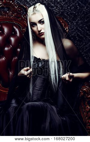 Gothic style. Beautiful woman with long blonde hair and black make-up wearing long black dress. Vintage interior, castle style. Halloween.