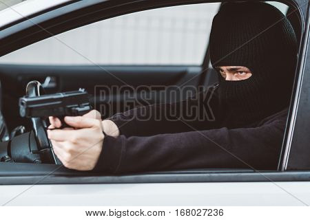 Man In Black Balaclava With Handgun Driving A Car.
