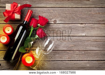 Valentines day greeting card. Red rose flowers, wine and gift box on wooden table. Top view with copy space