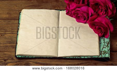 Red Roses And The Old Book On A Wooden Table In Vintage Style. Romantic St. Valentine's Day. Copy Sp