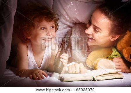 Magic times. Pretty delighted young mother reading a book to her lovely child using a flashlight while lying under the blanket.