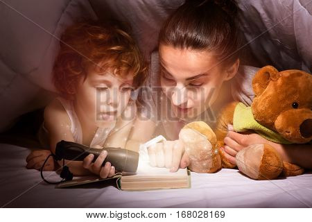 More stories. Happy delighted smiling mother and son reading a book with a flashlight while lying under the blanket together before going to sleep.