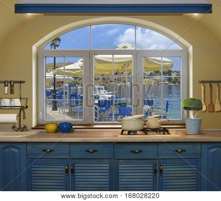Interior blue kitchen.Preparing lunch at home on the kitchen stove with a view from the window on the coastal cafe