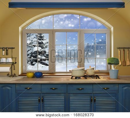 Interior blue kitchen. Preparing lunch at home on the kitchen stove with a view from the window on a snowy forest