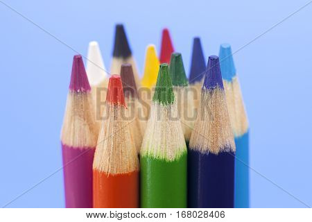 Close up of various coloring pencils with a blue background.