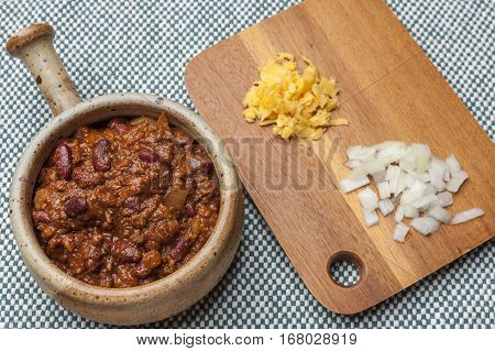 A close up image of a delicious bowl of chili with cheese and onions on a cutting board.
