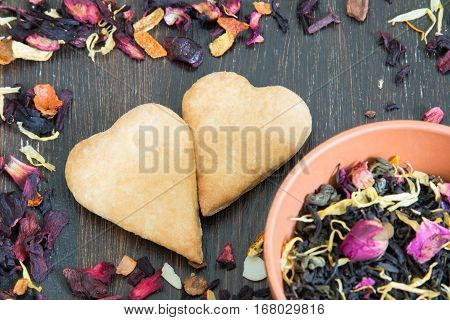 Leaves of tea and cookies in the shape of heart scattered on the wooden background