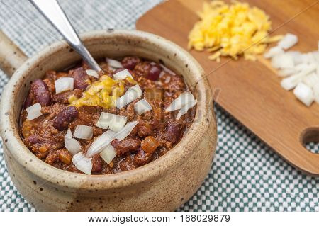 Spoon in delicious bowl of chili with cheese and onions on a cutting board.