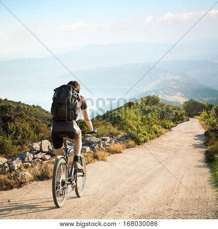 Rear View of a Man with Backpack Riding a Bicycle on in the Mountains by the Sea. Beautiful Nature Background. Healthy Lifestyle and Bike Travel Concept. Toned Photo with Copy Space.