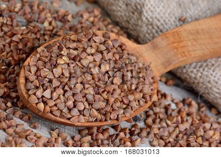 Buckwheat in a wooden spoon and jute canvas on table