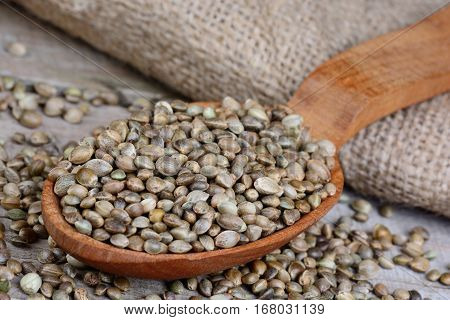 Hemp seeds in a wooden spoon and jute canvas on table