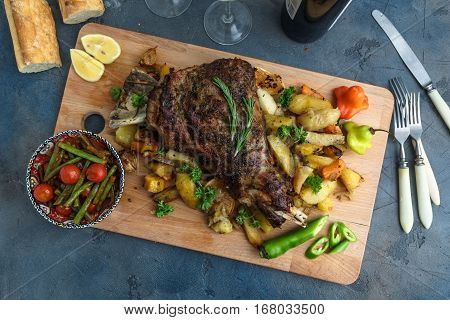 Roast Lamb Shoulder With Roasted Potatoes And Carrots Styled In A Rustic Wooden Board, Top View