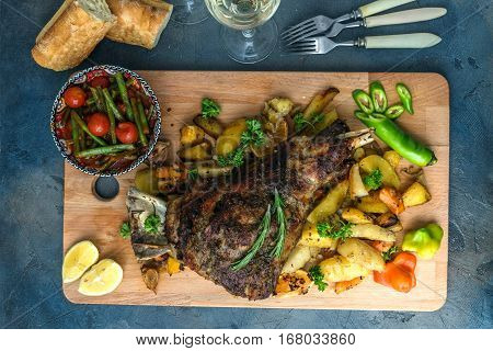 Roast lamb shank with roasted potatoes and carrots styled in a rustic wooden board, top view.