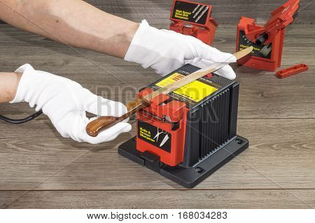 A person sharpens a knife with an electric sharpener
