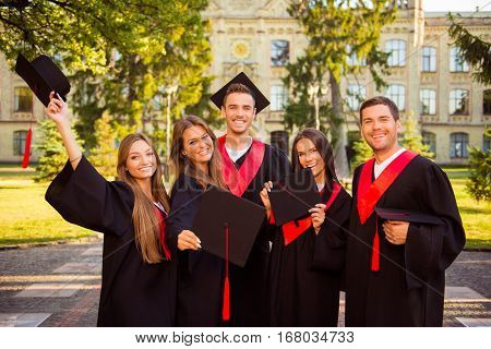 Successful Happy Five Graduates In Robes And Hats With Tassel Together Celebrating Graduation