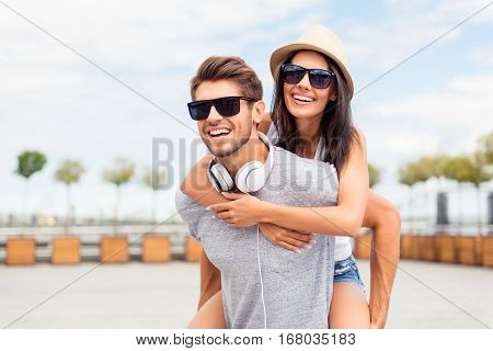 Handsome Man Carring His Smiling Girlfriend On Back