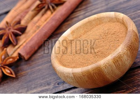 Cinnamon powder in a bowl with star anise and cinnamon sticks on wooden table