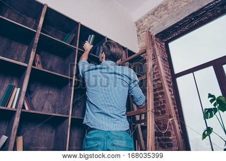 Rear View Of Man Standing On Stepladder And Searching Book In Library