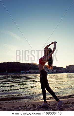 Silhouette of a slender healthy fit girl doing sports on sunset