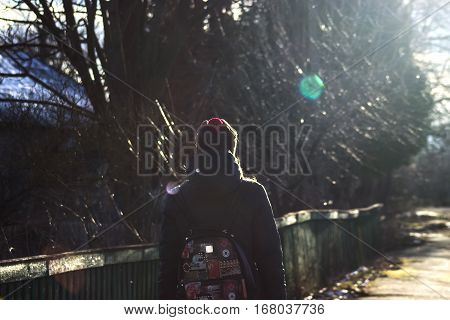 Girl hiker with backpacks walking at evening sunrays