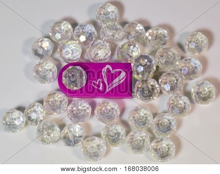 The pink USB flash drive with heart and gems on light background