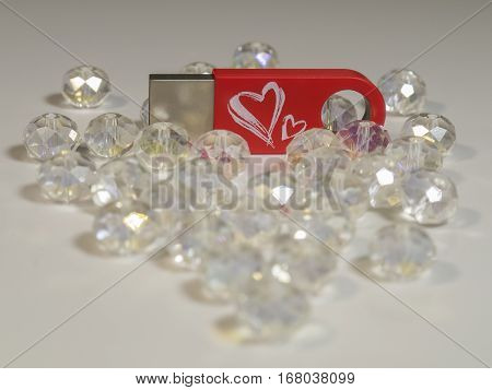 The red USB flash drive with heart and gems closeup