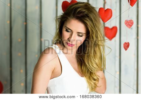 Beautiful blonde girl with blue eyes portrait in a white dress. Playing with hearts. Sexy look. Romantic scene. Red hearts and lights. Red and White background