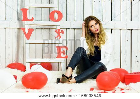Beautiful blonde girl portrait on Valentines Day. Being upset or irritated expression. Blue eyes and red lips wearing in a white jacket. Romantic scene. Red and White hearts on background