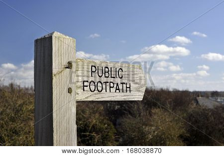 Wooden Public Footpath right of way finger post sign in the countryside.