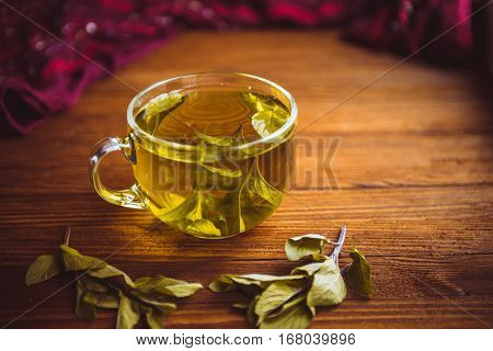 hot cup of tea from herbs stands on a brown wooden table