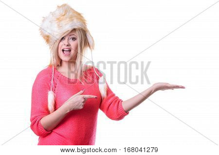 Outfit for cold days ideas fashion and clothing concept. Attractive smiling blonde woman wearing furry winter hat presenting something on palm hand