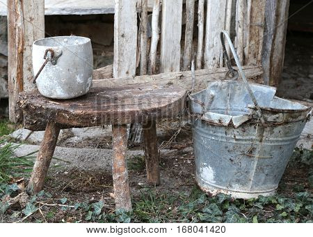 Old Broken Bucket And An Aluminum Pan On The Wooden Stool That W