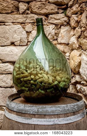 Big glass wine bottle half full of corks in the picturesque Eze village in south France