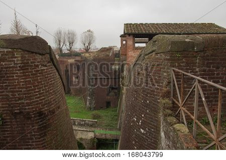 Italy Pistoia - November 27 2016: the view of brick walls and moat around Medici Fortress of Santa Barbara on November 27 2016 in Pistoia Tuscany Italy.