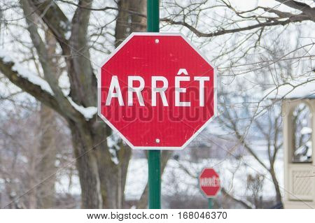 Stop sign from Quebec written in French in winter
