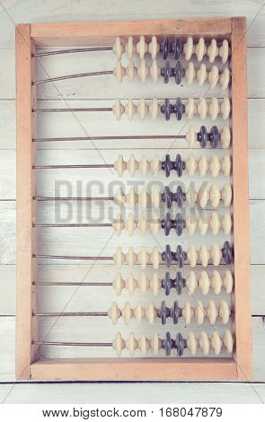 Old vintage retro abacus on wooden white background