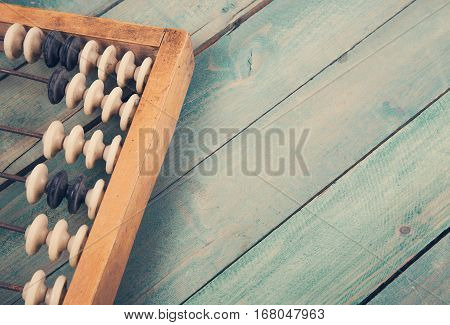 Old vintage retro abacus on wooden grunge background