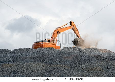 A huge digger fills it's bucket with the stone from the mountain of raw material it is standing on.