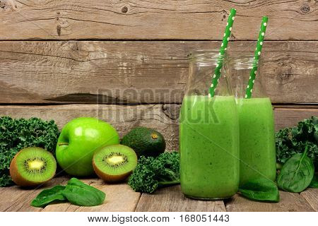Green Smoothie In Milk Bottles With Kale, Avocado, Spinach, Apple And Kiwi Against A Rustic Wooden B