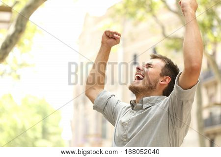 Portrait of an excited man raising arms in the street with buildings in the background