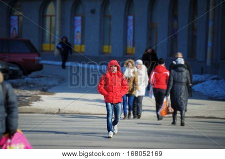 Daily life of urban residents in early spring. People go about their business on a bright Sunny day. Near the buildings in the shadow of snow. A man crossing the road