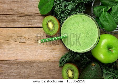 Green Smoothie Above View With Kale, Avocado, Spinach, Apple And Kiwi Against A Rustic Wooden Backgr