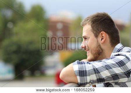 Side view of a happy man looking away and enjoying urban views from a balcony of a house or hotel