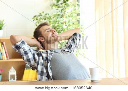 Portrait of a satisfied man relaxing with the arms in the head sitting on a chair at home with a warm light from a window